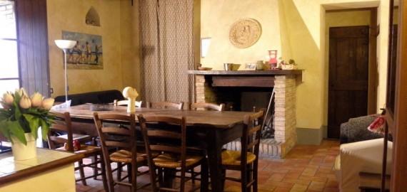 Ferienwohnung Meridiana - Wohnraum mit Essplatz am Kamin